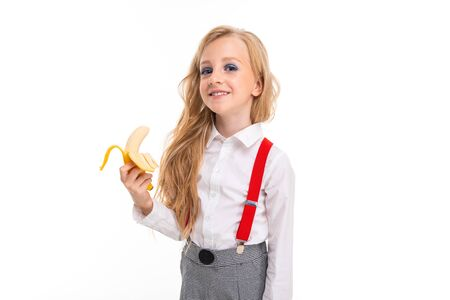 Little girl with long blonde hair in white shirt, red pull-ups, pants in cage, red socks and bolts with bright makeup with banana