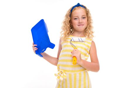 A little girl with red heap hair in a white and yellow striped summer suit, with a blue bandage on her head with a wall painting roller. Stockfoto