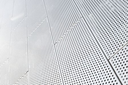 Metal grilles with many round holes in the ceiling background. Dot pattern on surface, diagonal view