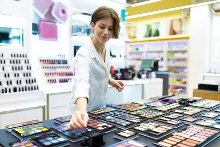Young smiling woman in cosmetics shop is testing eye-shadows. Photo with depth of field