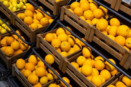 Diagonal view of wooden lug boxes with ripe lemons on counter in grocery store