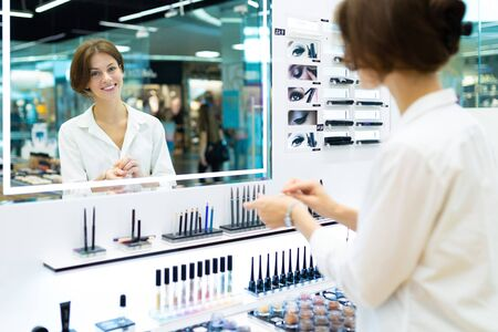 Young smiling woman in cosmetics shop is testing cosmetics. Photo with depth of field