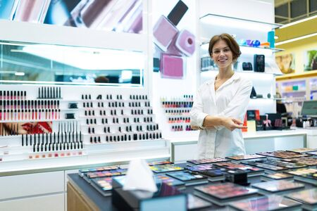 Young smiling woman in standing in cosmetics shop among shop-windows with cosmetics. Photo with depth of field Stok Fotoğraf