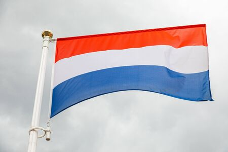 Dutch flag, on a flagstuff in front of the sky