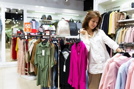 Young woman with fuschia color blouse in her hands in clothing shop. Photo with depth of field 版權商用圖片