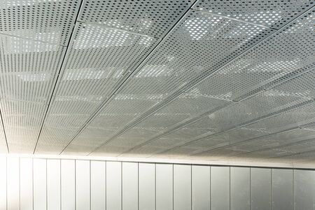 Diagonal view of metall grilles and round holes in metal ceiling surface, perforated panels. Archivio Fotografico