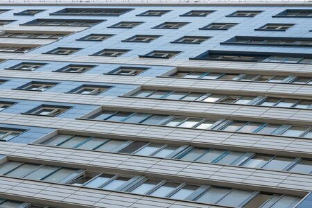 Ground view of tall building with blue and beige tiles on wall and big wide windows. Banco de Imagens