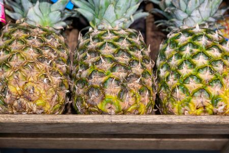 Wooden lug box with exotic pineapple on supermarket counter. Photo with depth of field Imagens