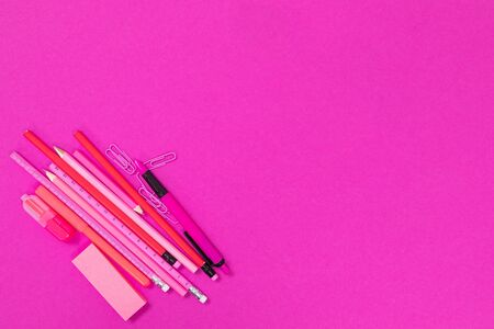 A group of pink office supplies is lying in the bottom left corner on pink surface cutout Stok Fotoğraf