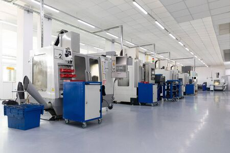 Row of equipment producing metal parts in clean new factory unit