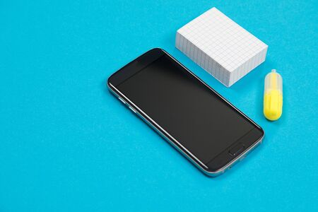 Black cellphone, pile of post-it and a yellow text marker on blue background isolated Stok Fotoğraf