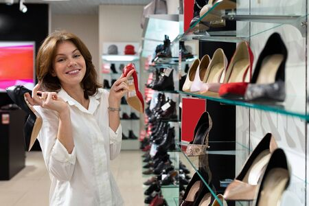 Woman holding black heeled shoe and red defocused heeled shoe in shop. Photo with depth of field