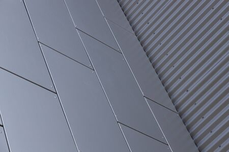 Bottom view of corner of building - junction of grey smooth tiled wall and grey metal corrugated wall