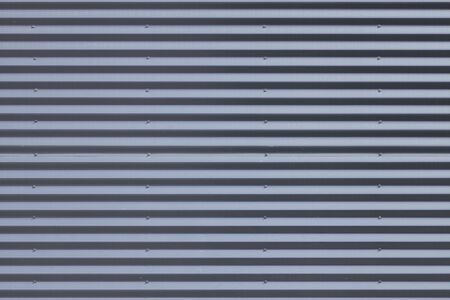 Close-up of grey metal ribbed wall in daylight Banque d'images - 131956523