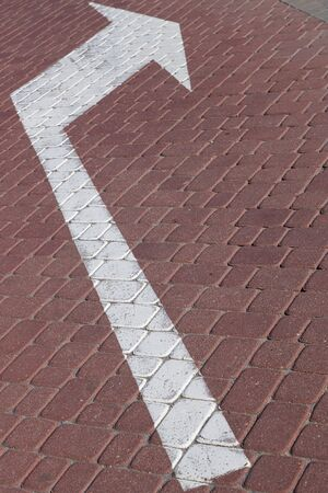 Close-up of white road marking arrow pointing to right side on maroon paving flag. Photo with depth of field