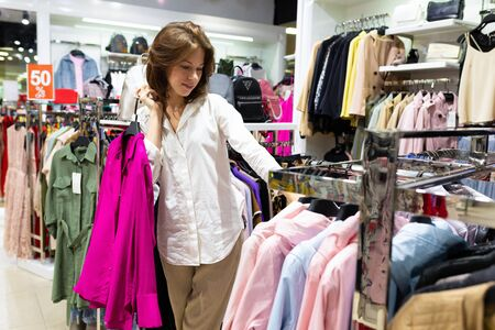Woman with fuschia color blouse in her hands in clothing shop. Photo with depth of field
