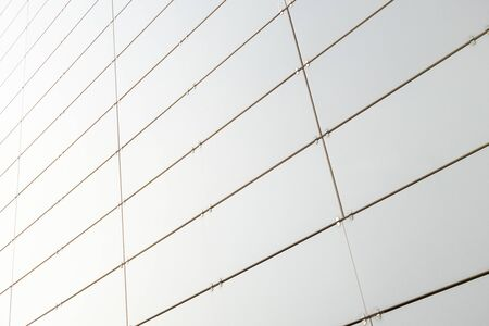 Ground view of white metal wall of a building made of small metal right angled sheets. Photo with depth of field
