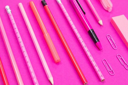 Close-up of straightly arranged group of rosy colour writing equipment on pink background isolated Zdjęcie Seryjne