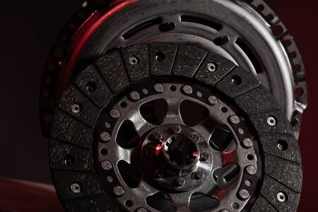 Two circle brake discs on dark red background. Disc brake rotors are metal discs that work together with the brake pads and calipers to slow the vehicle