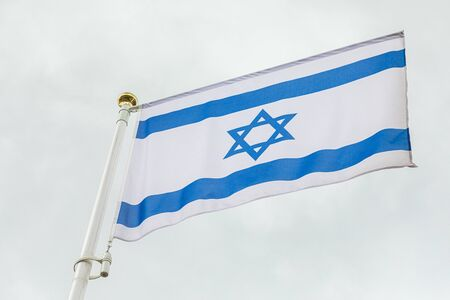 Israeli flag with blue six-pointed star wind against sky