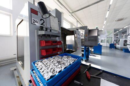 Moderne geautomatiseerde fabrieksapparatuur die metalen onderdelen verwerkt in het fabrieksgebouw. Foto met scherptediepte Stockfoto
