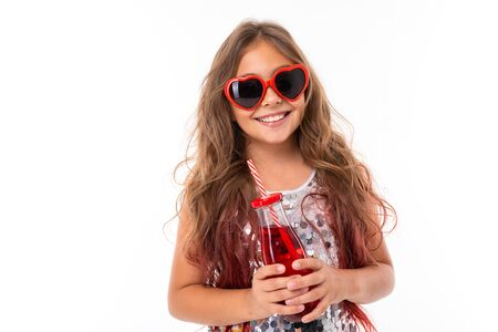 Girl in dark sunglasses holding juice in her hands.