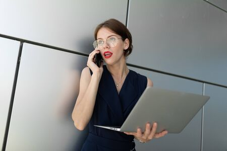 portrait of a business woman. speaks on the phone, holds a laptop in his hands, looking to the side. Shot on aluminum wall background