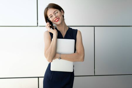 young businesswoman with a laptop in her hands talking on the phone. Business portrait on a gray wall background
