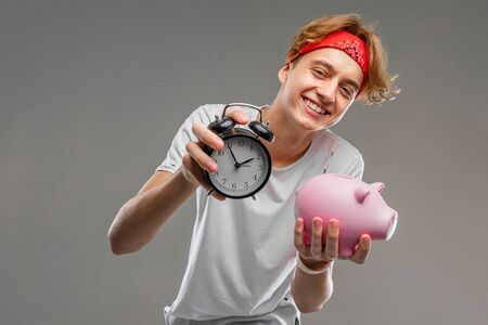 teenager with clock and piggy bank, prankster concept