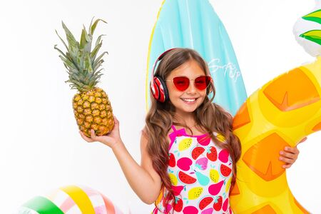 closeup smiling girl on a white background, the child holds a pineapple in his hands surrounded by swimming accessories, red headphones on his head. Stok Fotoğraf
