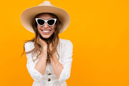Brunette in a hat and sunglasses of a yellow wall, half-length portrait