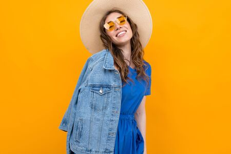 Hipster girl against the yellow wall, half-length portrait of a woman in a hat and sunglasses Stock fotó