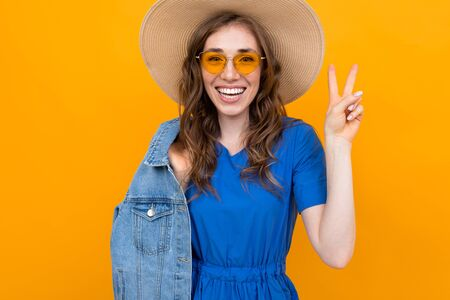Stylish girl with a wide smile on her face shows ok, wipes the brown-haired woman in yellow glasses
