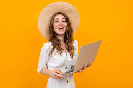 Portrait of a young girl of yellow wall with a laptop in her hands