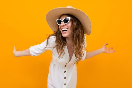 Stylish young woman in a hat on a yellow Stock fotó