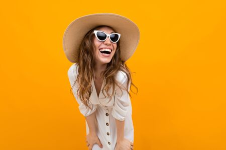Girl in a hat and glasses against the yellow wall laughs with a wide smile Stock fotó