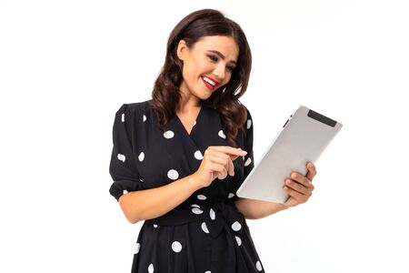 Young girl with delightful smile, flat teeth, red lipstick, long wavy chestnut hair, beautiful makeup, in black and white dress in peas holds a tablet.