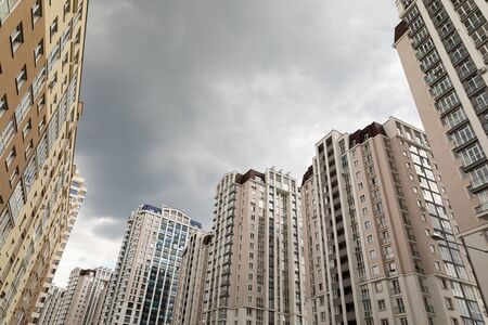 Cloudy weather, autumn sky with dark clouds. Many apartment buildings standing in front of each other. Stockfoto