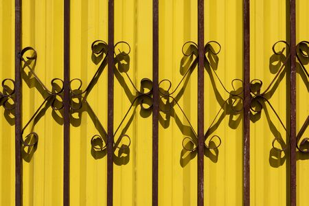 Wrought iron railing against bright yellow background Stock Photo