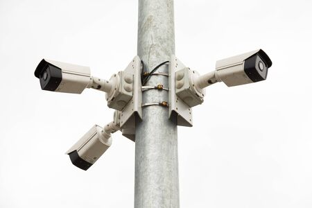 Three white cctv cameras on metal pile on street