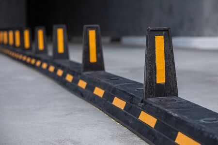 Road dividers with yellow sticks on road to underground garage. Photo with depth of field Stock Photo