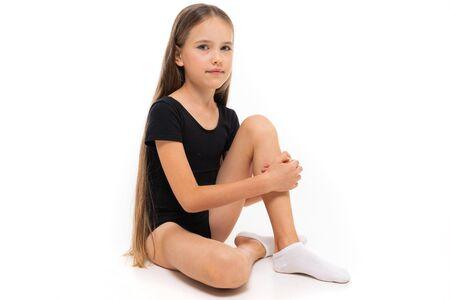 Imagen de una niña gimnasta sentada en calcetines blancos crujientes y trico negro de altura completa.