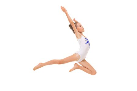 girl gymnast in white trico in full height performs in a white jump