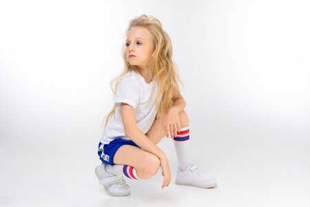 Fashion girl blonde with long hair in sports shirt, shorts, sneakers sits and looks aside Foto de archivo