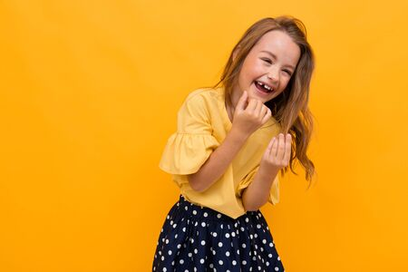 charming girl child laughs on an orange background Imagens