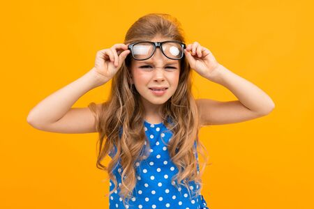 schoolgirl with glasses raises glasses over her eyes, poorly seeing child