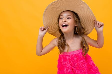 naughty cheerful girl in a pink dress and a straw hat on a background of a yellow wall