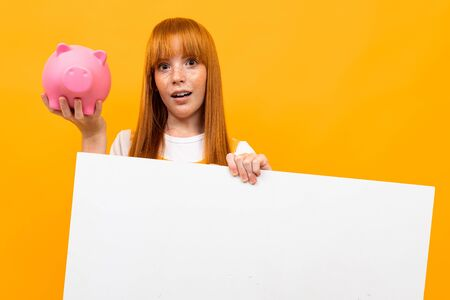 beautiful red-haired girl with a piggy bank and a blank banner on an orange background Stockfoto