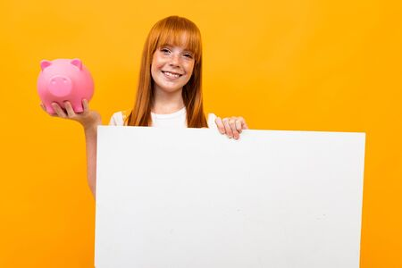 red-haired cute girl with a wide smile on an orange background with a piggy bank in hands, blank form for text, banking and insurance concept