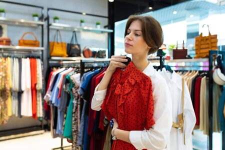 Young thoughtful woman is holding dress in clothing shop. Photo with depth of field